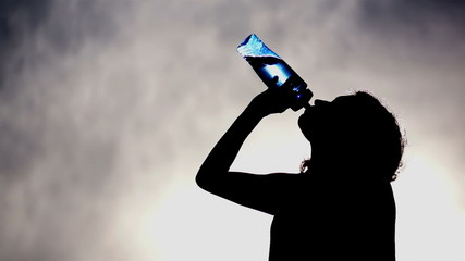 Silhouette of a Woman Drinking Water
