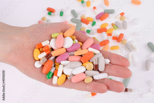 Hand with a pills on gray background