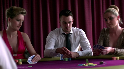 Man betting poker with two girls