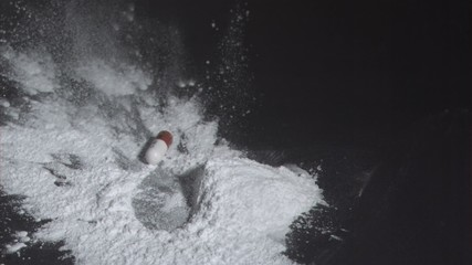 Tablet capsule falling into powdered drug