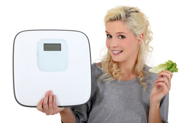 woman showing a bathroom scale and taking a lettuce