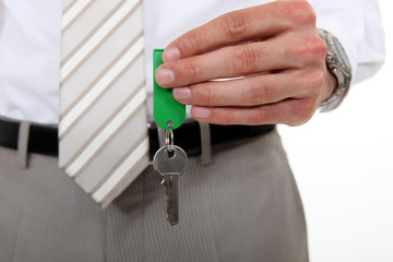 man in a suit holding a key