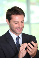 Man in suit looking at mobile