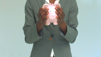 Businesswoman shaking coins out of piggy bank