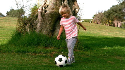 Child dribbling with the football