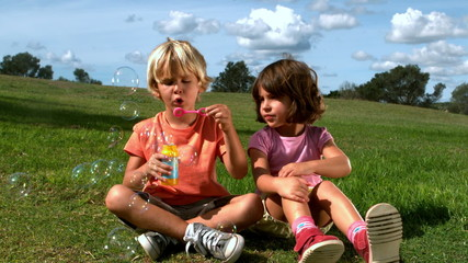 Boy blowing bubbles with a girl