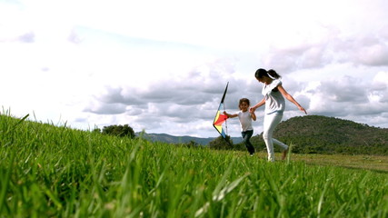 Mother and daughter running with kite