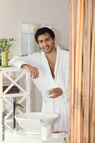 Man drinking a glass of water in his bathroom