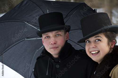 Tired man and happy woman under umbrella