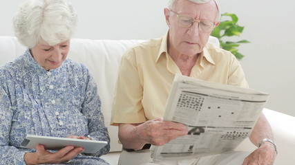 Old couple using a tablet and a newspaper