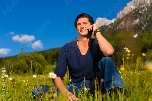 man with phone  sitting in the mountains