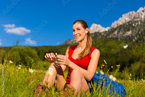 woman sitting in meadow with mountain view