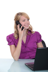 businesswoman sitting at her desk and talking on the phone