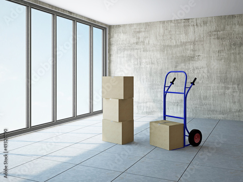 Empty room with boxes and pushcart