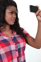 African woman taking pictures with phone