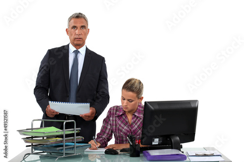 Boss delegating work to female employee