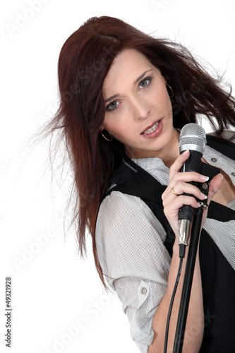 Sultry brunette singing into microphone