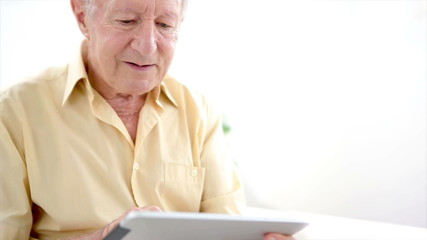 Old man touching a tablet