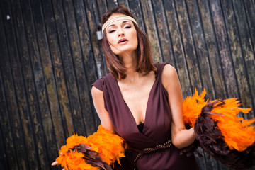 singing actress in brown and orange boa