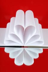 Kartki z zeszytu w kształcie serca na czerwonym tle.