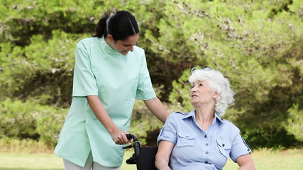 Nurse talking to an old woman in a wheelchair