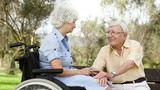 Elderly man sitting on park bench talking to his partner in