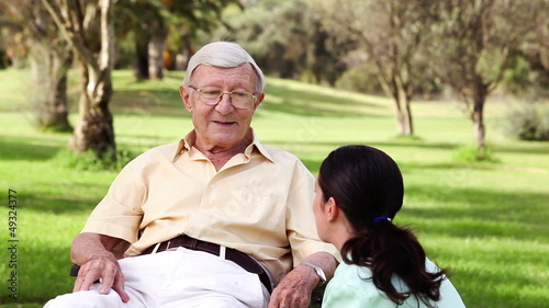 Old man talking with a nurse crouched