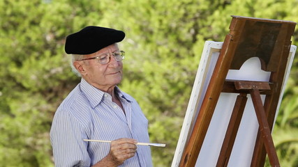Portrait of elderly man in a beret painting in the park