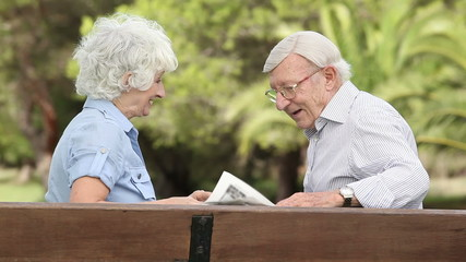Old couple laughing on a bench with newspaper