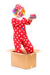 A smiling clown in a cardboard box holding a gift