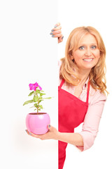 A smiling agricultural woman holding a flower pot and posing beh