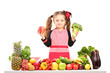 Girl with apron holding a broccoli and red apple behind a table