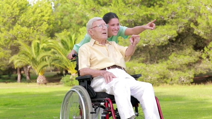 Nurse walking an old man in wheelchair