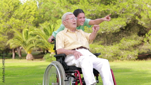 Nurse walking an old man in wheelchair