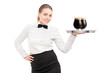 A waitress with bow tie holding a tray with two glasses of dark