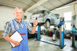 Mechanic holding a car key atauto repair shop during an automobi