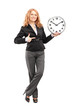 Blond mature woman standing and pointing on a wall clock