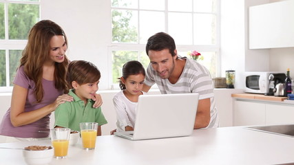 Family using a white laptop in kitchen