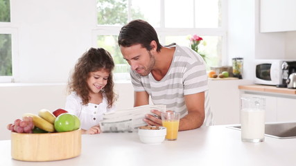 Father and his daughter reading newspaper