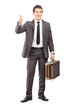 Young businessman holding a briefcase and giving thumb up