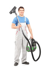 Full length portrait of a young male worker holding a vacuum cle
