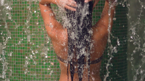 Woman taking a tropical shower in a spa