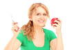 Smiling woman holding a red apple and tooth brush