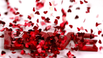 Lots of heart confetti falling on the love text