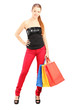 Full length portrait of a woman with shopping bags looking at ca