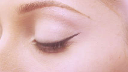 Makeup artist applying false eyelashes to model's eyes.