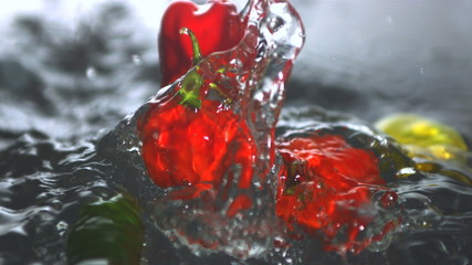Many chili peppers falling in water