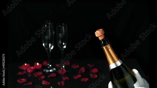 Champagne cork popping in front of two flutes