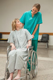 Nurse wheeling a female patient sitting on a wheelchair