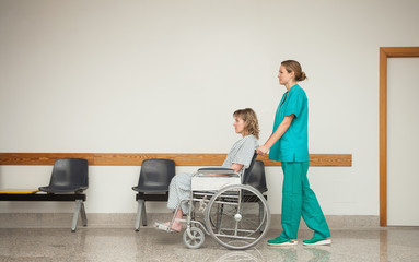Nurse pushing the wheelchair of a female patient